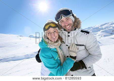 Cheerful couple having fun at top of ski slope