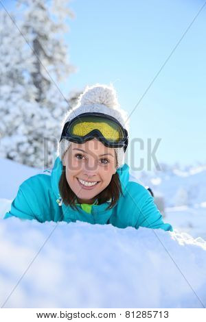 Cheerful girl in ski outfit laying down in snow