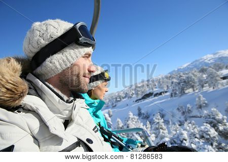 Couple of skiers going up ski slope with chairlift