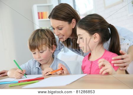 Mother watching kids at home while they are drawing