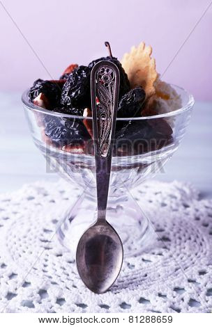 Dessert with prunes in glass bowl on wooden table and light background
