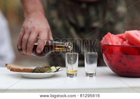 Man Filling Glasses Of Brandy