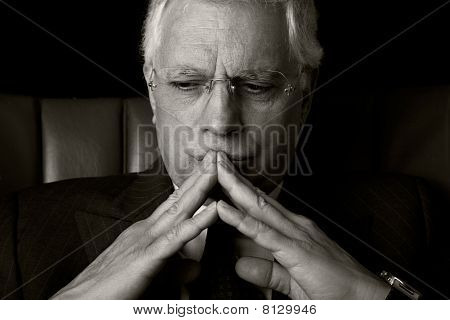 Old Businessman  Seated On A Chair, Thinking, Isolated On Black Background, Studio Shot