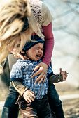 foto of crying boy  - mother and crying child in the park on a sunny day in early spring - JPG