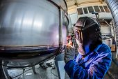 foto of manufacturing  - Man welding with reflection of sparks on visor - JPG