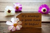 picture of purple white  - Brown Label With Life Quote Its Always A Good Time To Begin With Purple And White Cosmea Blossoms On Wooden Background Vintage Retro Or Rustic Style