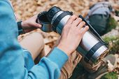 foto of thermos  - Hiker woman pours tea or coffee from thermos to cup in autumn forest - JPG