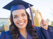 stock photo of graduation gown  - Happy Graduating Mixed Race Woman In Cap and Gown Celebrating on Campus - JPG