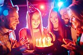 pic of congrats  - Pretty girl with birthday cake and her friends looking at burning candles at party - JPG