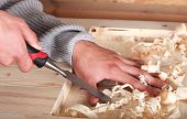 stock photo of gad  - Human hands in wood work with chisel - JPG