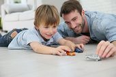 stock photo of daddy  - Daddy with little boy playing with toy cars - JPG