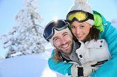 foto of piggyback ride  - Man giving girlfriend piggyback ride in the snowy mountain - JPG