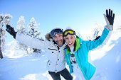 image of cheer-up  - Cheerful couple of skiers lifting arms up - JPG
