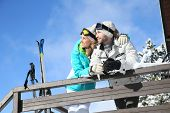 image of log cabin  - Couple of skiers admiring panorama from log cabin - JPG