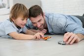 stock photo of playtime  - Daddy with little boy playing with toy cars - JPG