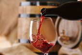pic of life event  - Pouring red wine from bottle into glass with wooden wine casks on background - JPG