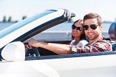 foto of road trip  - Happy young couple enjoying road trip in their white convertible while both looking at camera and smiling - JPG