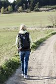 picture of girl walking away  - back of walking girl with jeans and backpack - JPG