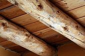 picture of rafters  - Hefty log rafters in a rustic structure hold up the ceiling and roof.