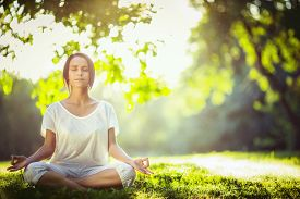 foto of adults only  - Young girl meditating in the park - JPG