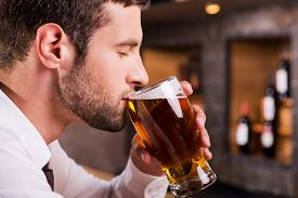 image of cold drink  - Side view of handsome young man drinking beer while sitting at the bar counter - JPG