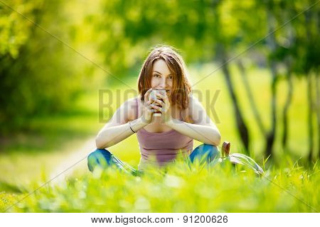 Young woman with takeaway coffee outdoors on sunny summer day
