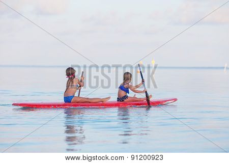 Little cute girls swimming on surfboard during summer vacation