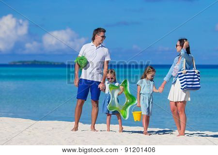 Happy family during summer vacation on white beach