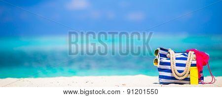 Stripe bag, blue towel, sunglasses, sunscreen bottle and swimsuit on white beach