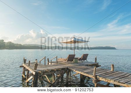 Summer, Travel, Vacation And Holiday Concept - Beach Chairs And Umbrella On Wooden Desk Against Blue