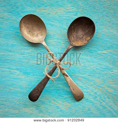 Two Old Crossed Vintage Spoons On Blue Wooden Background, Top View