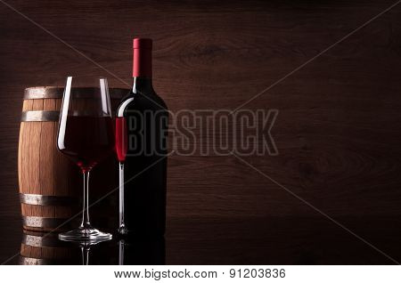 Bottle Of Red Wine, Glass And Barrel On Dark Wooden Background