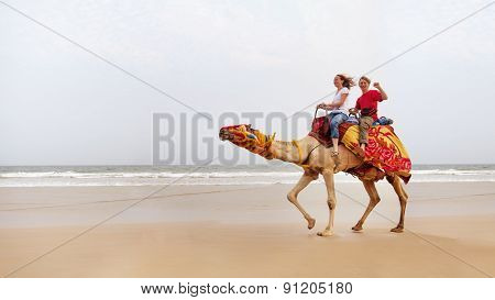 Young Couple Is Riding A Camel On The Sea Background.