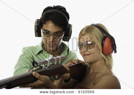 man teaches woman to shoot