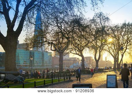 LONDON, UK - APRIL 15, 2015: Tower park in sun set. River Thames side walk with people resting by th