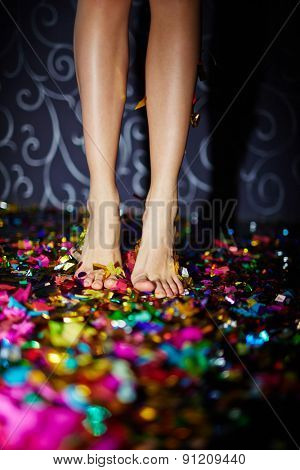 Barefoot female standing on the floor with confetti
