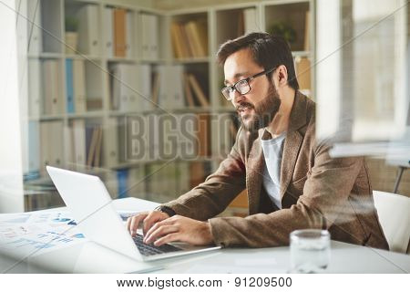 Young businessman typing in office