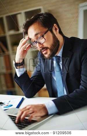Asian businessman browsing in laptop in office
