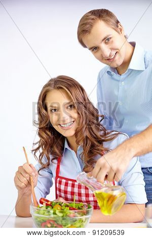Happy couple cooking vegetable salad