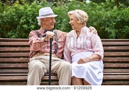 Happy senior couple sitting on bench in park and talking