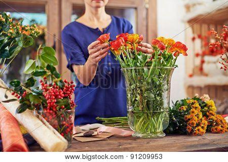 Female florist touching fresh flowers during work in studio