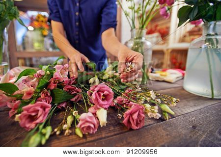 Female florist sorting flowers in workshop