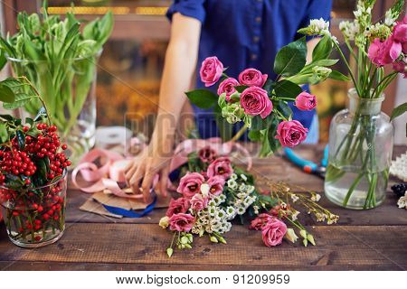 Fresh flowers and ripe berries with designer standing near by