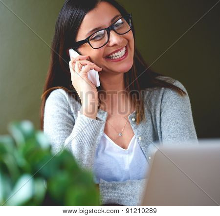 Woman Smiling Widely While Talking On Mobile Phone.