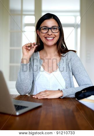Woman Sitting Upright Smiling At Home Office Desk.