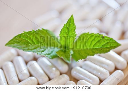 Capsules and a sprig of mint on a wooden surface