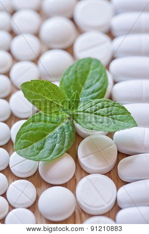 Different White Pills And Foliage Mint On A Wooden Background