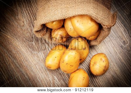 Raw potatoes in the sack on wooden background