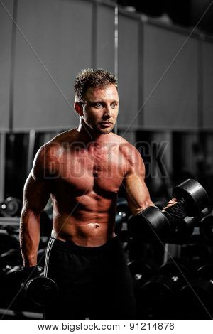 Handsome Man With Dumbbells Workout In Gym