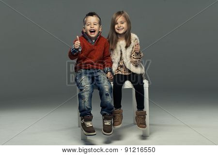 A Portrait Of A Laughing Girl And A Smiling Boy. Thumbs Up